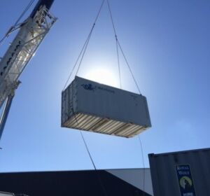 A crane hired to lift a refrigerated shipping container over a building in Frewville